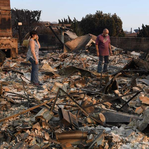 John and Julie Wilson sort through the remnants of their burnt out home after the Thomas Fire swept through Ventura on Dec. 6, 2017. (Credit: AFP PHOTO / MARK RALSTON)