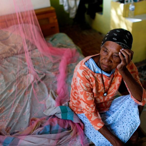 Aurea Cruz, 66, sits on her bed inside her house damaged by Hurricane Maria in Vieques, Puerto Rico, on Nov. 26, 2017. (Credit: Ricardo Arduengo / AFP / Getty Images)