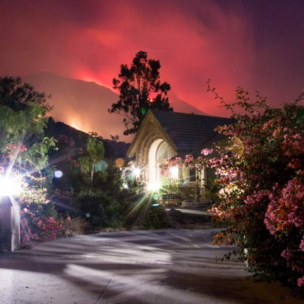 The Thomas Fire burns behind houses in Ojai on Dec. 7, 2017. (Credit: AFP PHOTO / Kyle Grillot)