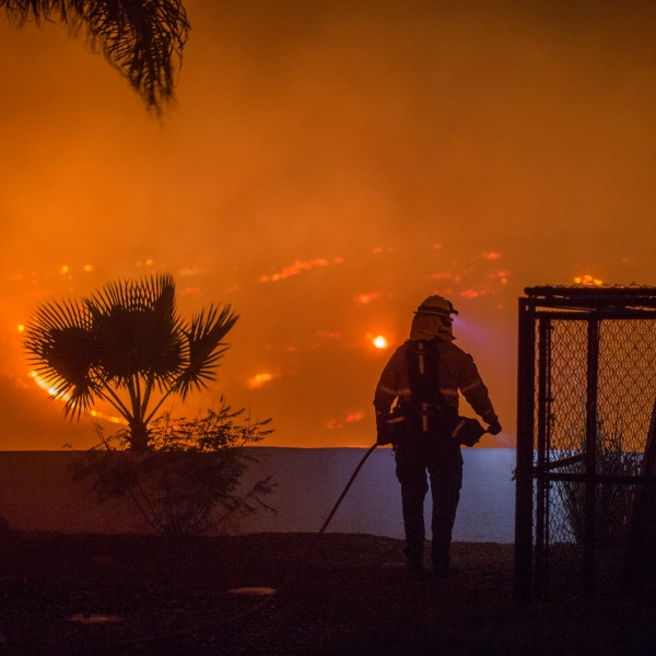 A firefighter guards a house at the Lilac Fire on Dec. 7, 2017 near Bonsall, California. (Credit: David McNew/Getty Images)
