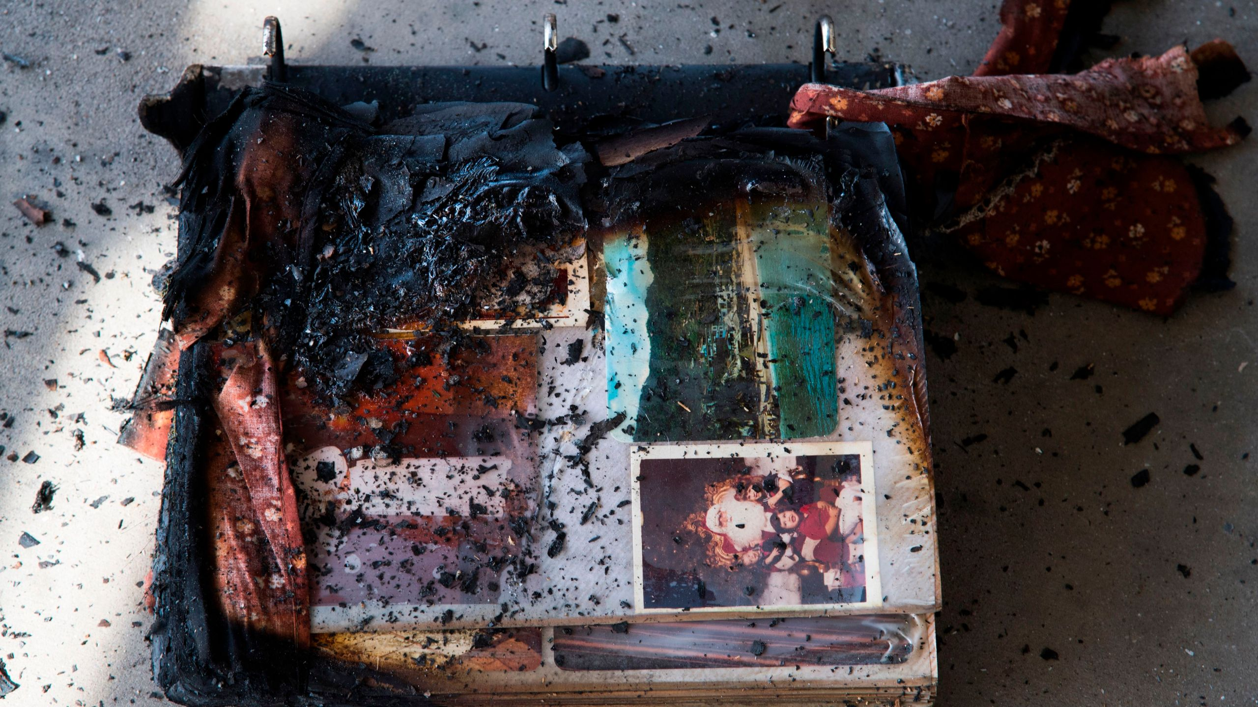 A photo album damaged by fire is see amid the destruction of the Lilac Fire, Dec. 8, 2017, at a retirement community in Fallbrook. (Credit: AFP PHOTO / Robyn Beck)