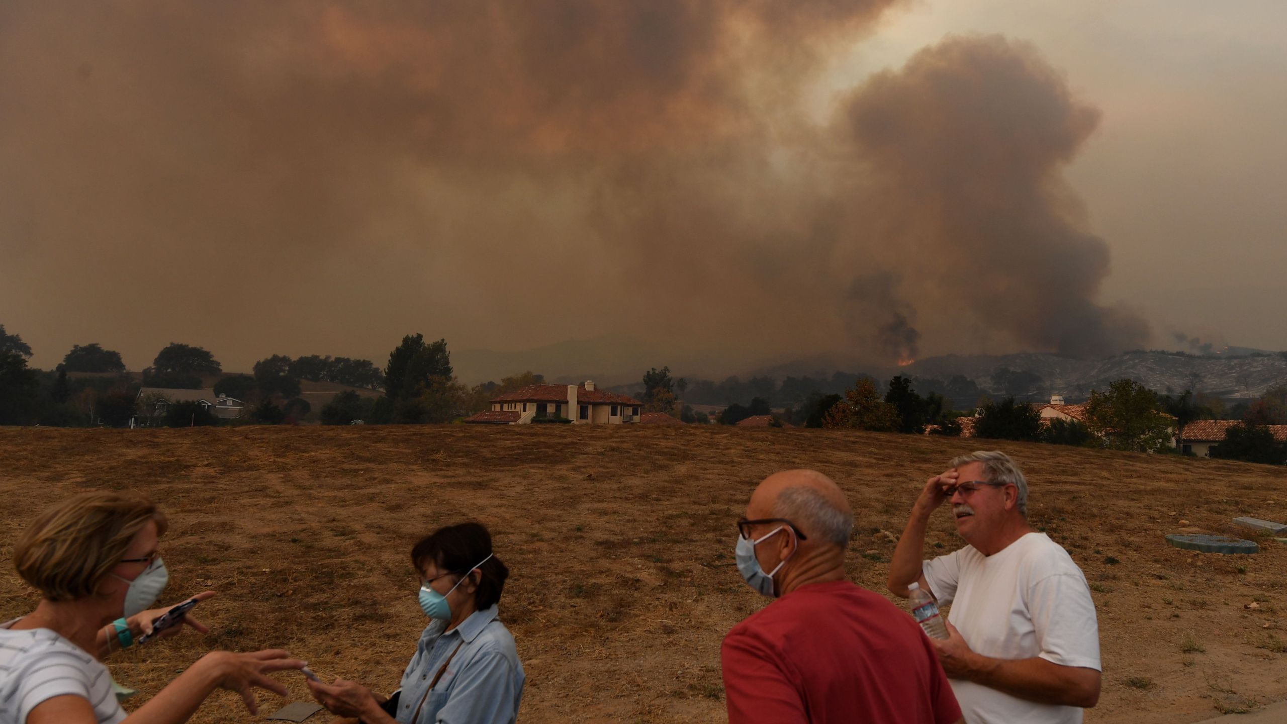 Local residents keep watch while fire and smoke from the Thomas wildfire heads towards their housing estate in Ojai on Dec. 9, 2017. (Credit: Mark Ralston / AFP / Getty Images)