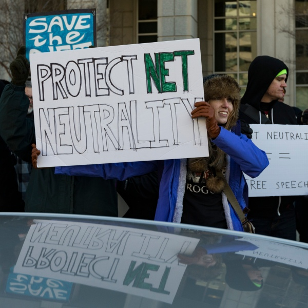 A demonstrator holds a 'Protect Net Neutrality' protest sign during a demonstration against the proposed repeal of net neutrality outside the Federal Communications Commission headquarters in Washington, DC on December 13, 2017. (Credit: ALEX EDELMAN/AFP/Getty Images)