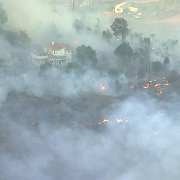 Flames surround a home in the Liberty Fire near Murrieta on Dec. 7, 2017. (Credit: KTLA)