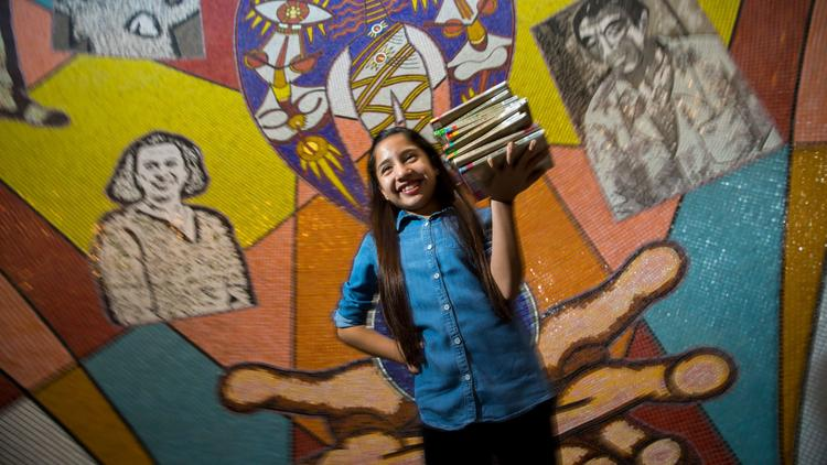"""Leilany Medina, 11, holds a stack of books from her favorite series, """"Judy Moody,"""" at the East Los Angeles Library, where she """"read away"""" late fees last week. Students won't have to worry about new late fees because of just-approved library rules. (Credit: Jay L. Clendenin / Los Angeles Times)"""