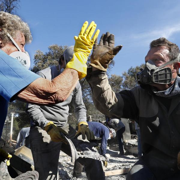 Leona Mote, left, high-fives Trevor Quirk as a team of volunteers helps sift through the rubble of her home near Ojai that burnt to the ground in the Thomas fire. Among the items recovered were her husband's wedding band, jewelry and part of a coin collection. (Credit: Mel Melcon / Los Angeles Times)