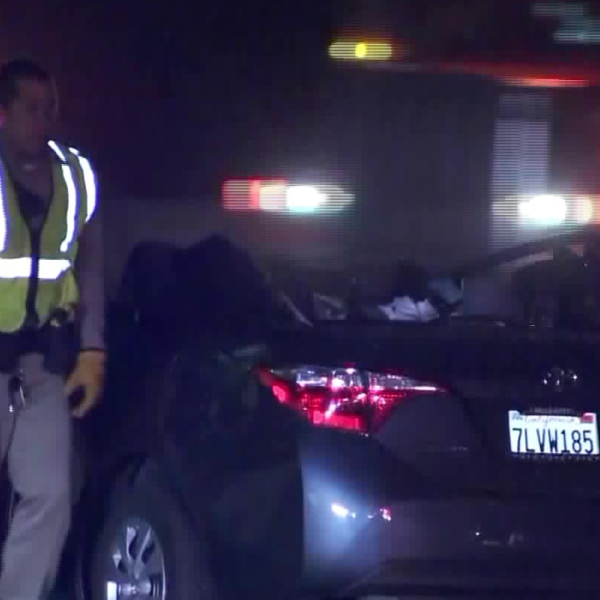 An official walks past a car involved in a head-on collision involving a wrong-way driver that happened along the 210 Freeway near Lake View Terrace on Dec. 17, 2017. (Credit: KTLA)