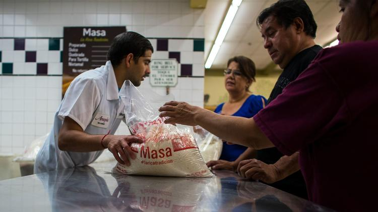 Grocery store clerk Hector Esparza hands out masa to customers at Amapola Market in Downey. During Christmas 2016, numerous customers returned masa purchased at Amapola seeking refunds. (Credit: Gina Ferazzi / Los Angeles Times)