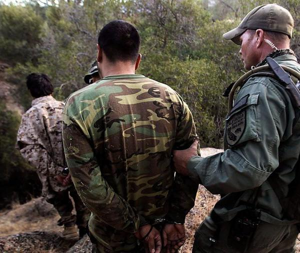 Wardens with the California Department of Fish and Game detain a pair of men during a raid on an illegal marijuana growing operation in the Sierra Nevada foothills in 2012. (Credit: Luis Sinco / Los Angeles Times)