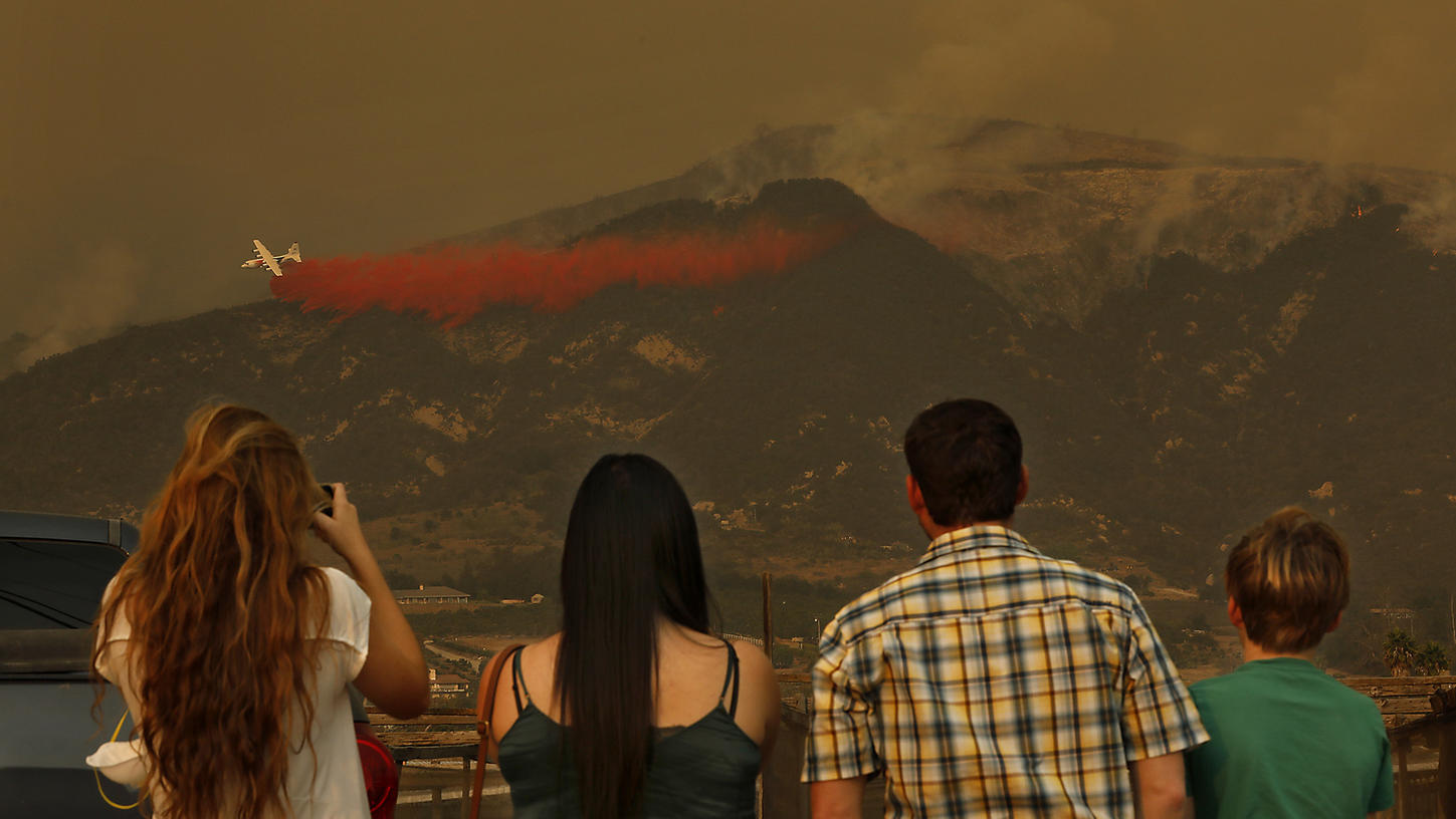 People watch as a plane makes a drop in Carpinteria on the Thomas Fire during the week of Dec. 11, 2017. (Credit: Mel Melcon / Los Angeles Times)