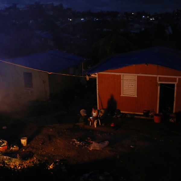 A resident sits outside her home, which lacks electricity, as a trash fire burns on December 21, 2017 in San Isidro, Puerto Rico. (Credit: Mario Tama/Getty Images)