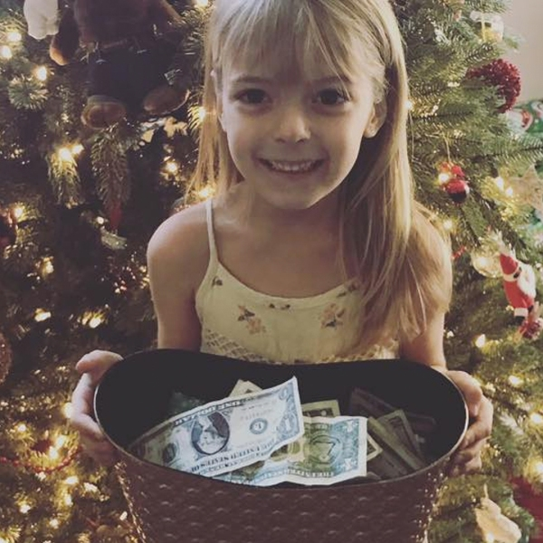 Faye Segraves is seen in a family photo with the money she collected for the Wildland Firefighter Foundation.