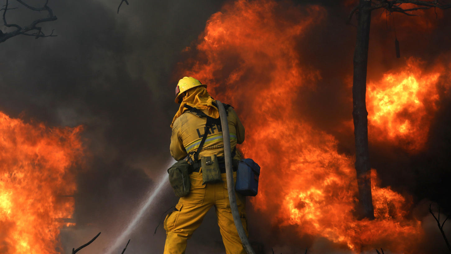Firefighters try to save a home along Linda Flora Drive in Bel Air, where the Skirball Fire is burning Dec. 6, 2017. (Credit: Genaro Molina / Los Angeles Times)