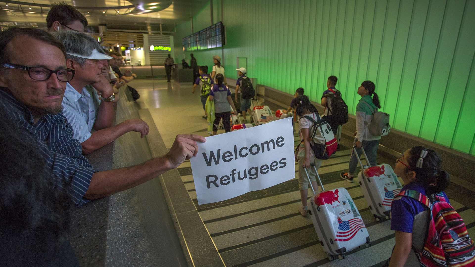 John Wider carries a welcome sign near arriving international travelers on the first day of the the partial reinstatement of the Trump travel ban, temporarily barring travelers from six Muslim-majority nations from entering the U.S., at Los Angeles International Airport (LAX) on June 29, 2017, in Los Angeles. (Credit: David McNew/Getty Images)