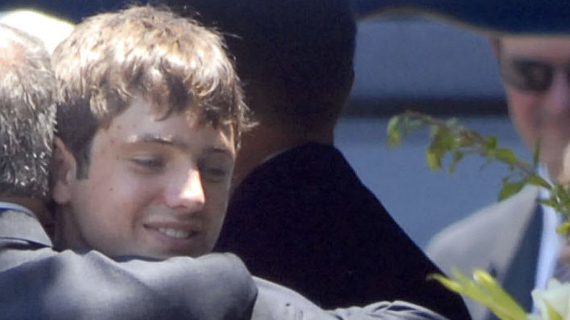 Burke Ramsey is embraced by his father at the grave of JonBenet Ramsey after a funeral service for his mother Patsy Ramsey June 29, 2006 in Marietta, Georgia. (Credit: Barry Williams/Getty Images)