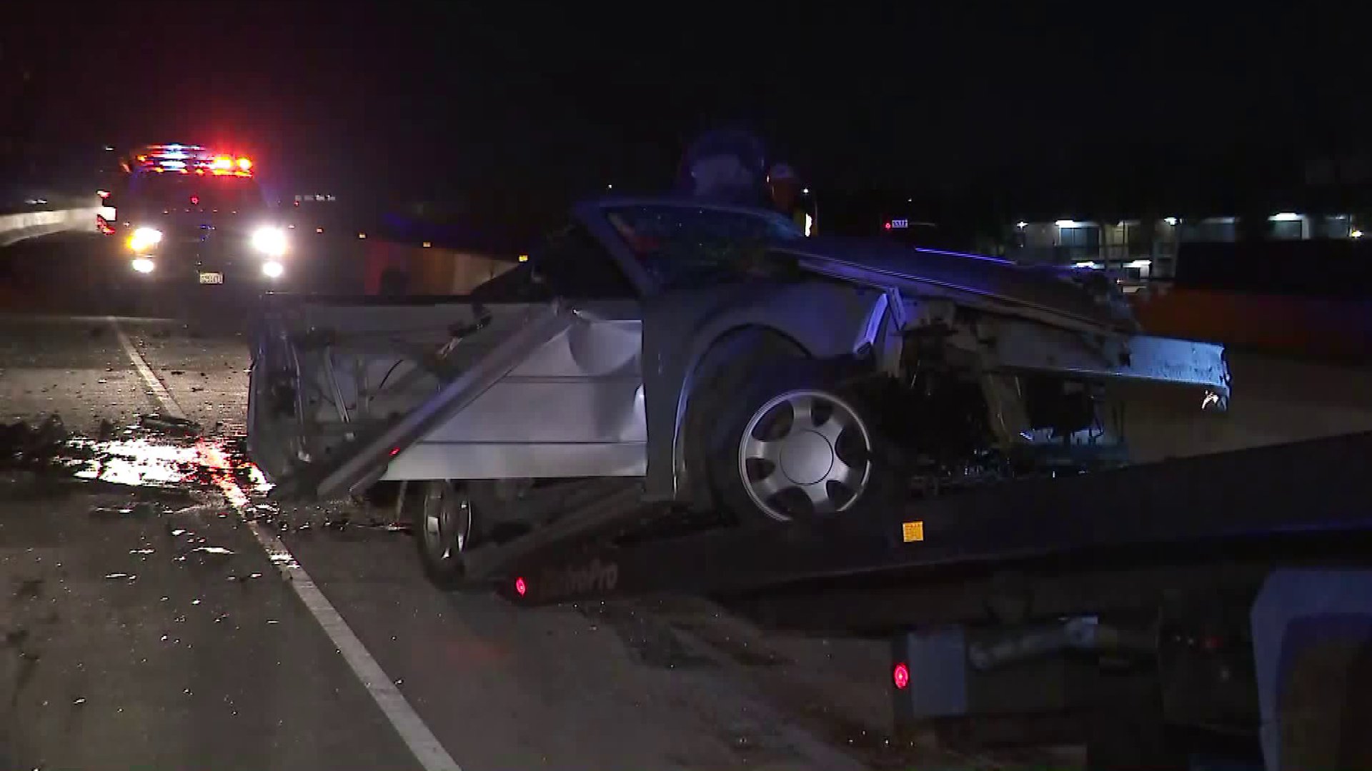 A badly-damaged vehicle involved in a wrong-way crash in Santa Ana is towed from the 55 Freeway on Jan. 5, 2018. (Credit: KTLA)