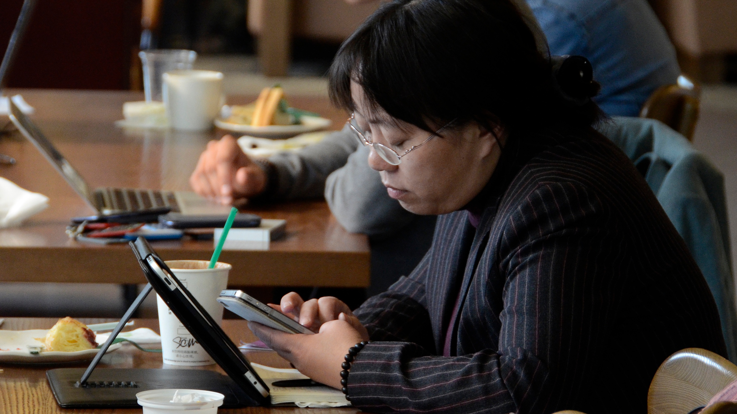 A woman uses her iPhone and iPad at a cafe in Beijing on Nov. 2, 2012. (Credit: Wang Zhao / AFP / Getty Images)