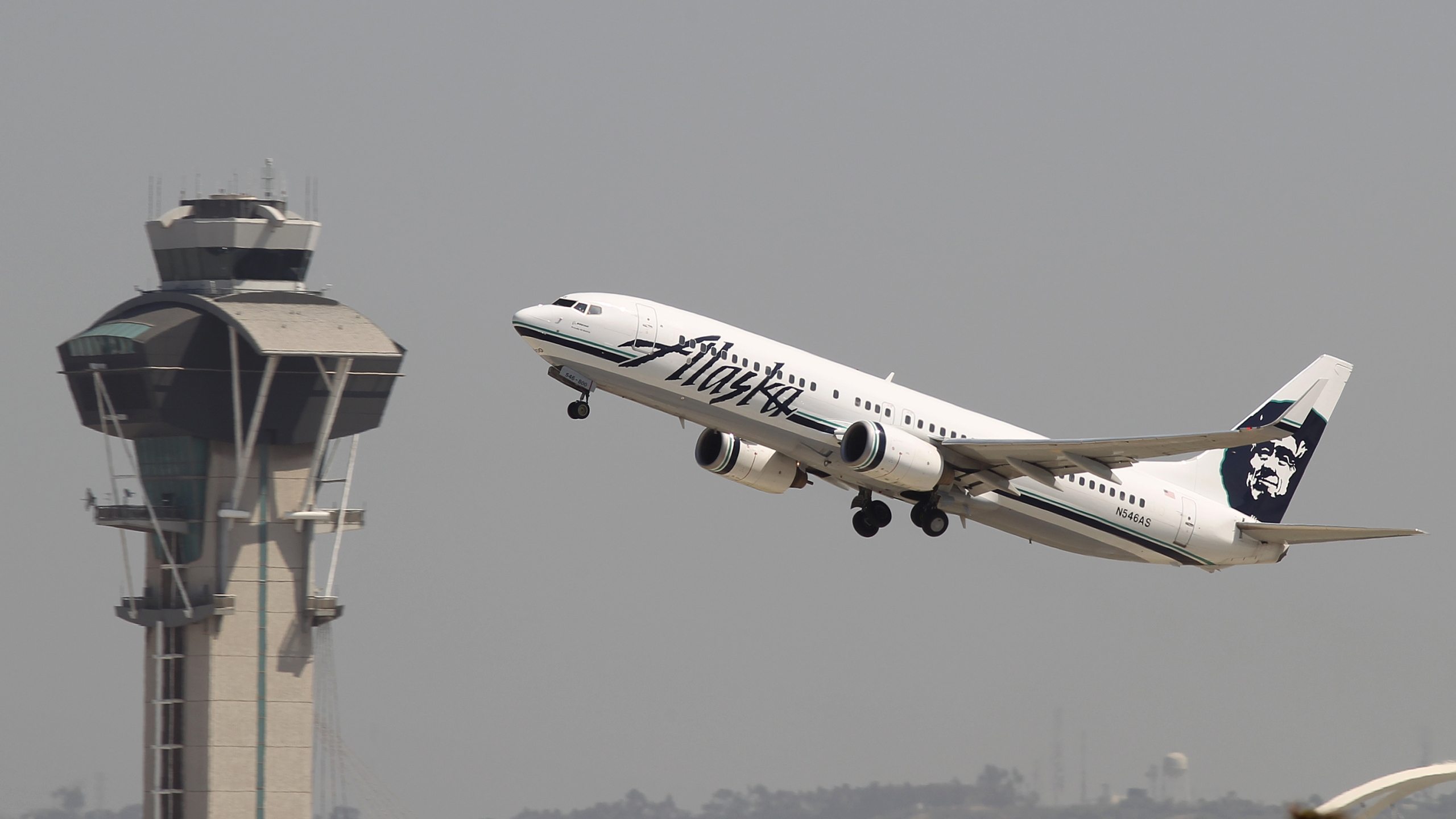 An Alaska Airlines jet passes the air traffic control tower at Los Angeles International Airport during take-off on April 22, 2013. (Credit: David McNew/Getty Images)