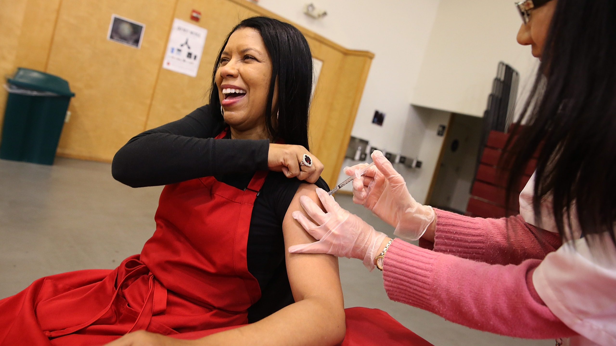 Cynthia Foreman receives a free flu shot from a Walgreens employee during a free flu shot clinic at Allen Temple Baptist Church on Dec. 19, 2014, in Oakland. (Credit: Justin Sullivan/Getty Images)