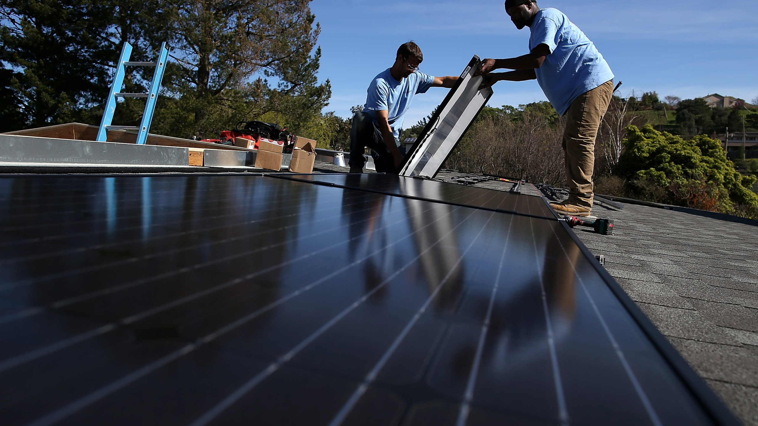 Craig Powell and Edwin Neal install solar panels on the roof of a home on Feb. 26, 2015 in San Rafael, California. (Credit: Justin Sullivan/Getty Images)