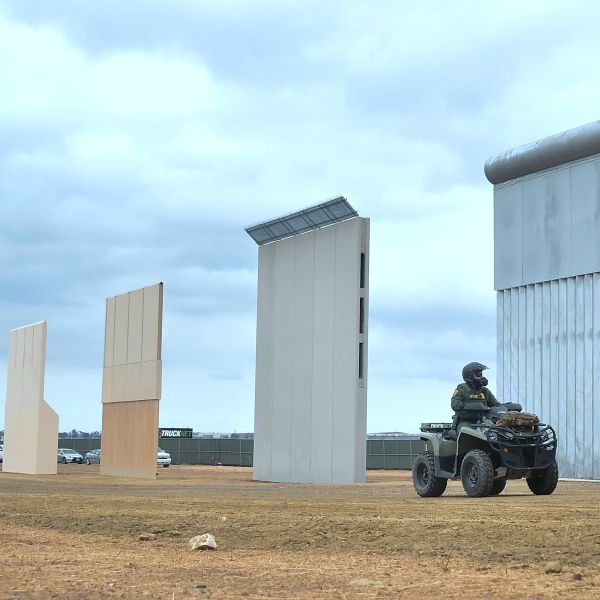 A Homeland Security border patrol officer rides an All Terrain Vehicle (ATV) past prototypes of President Donald Trump's proposed border wall on Nov. 1, 2017, in Otay Mesa. (Credit: Frederic J. Brown / AFP / Getty Images)