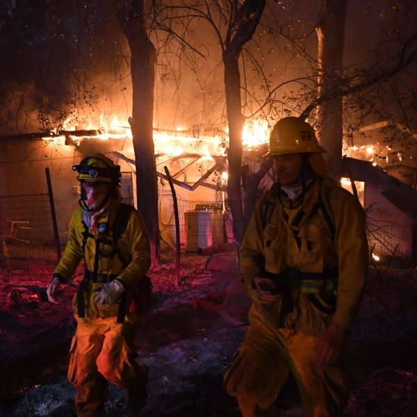 Firefighters move away from a burning house after discovering downed live power lines, as the Thomas wildfire continued to burn in Carpinteria, California, on Dec. 10, 2017. (Credit: Mark Ralston / AFP / Getty Images)