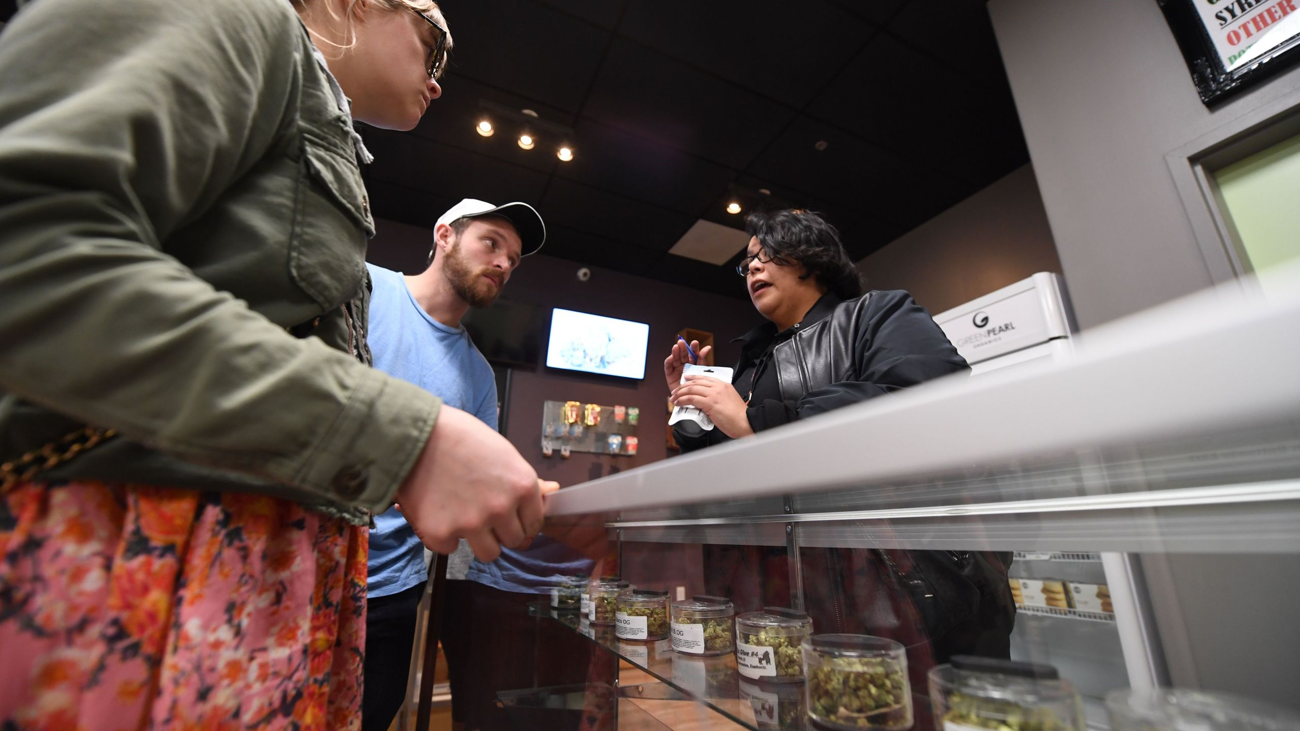 Tourists Laura Torgerson and Ryan Sheehan, visiting from Arizona, talk to a budtender at the Green Pearl Organics dispensary on the first day of legal recreational marijuana sales in California on Jan. 1, 2018 in Desert Hot Springs. (Credit: ROBYN BECK/AFP/Getty Images)