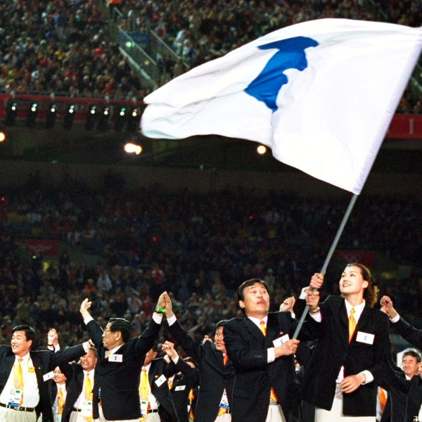 The two Korean Olympic teams walk round together under the same flag in a gesture of reconciliation during the Opening Ceremony of the Sydney 2000 Olympic Games at the Olympic Stadium in Homebush Bay, Sydney, Australia. (Credit: Jed Jacobsohn /Allsport)