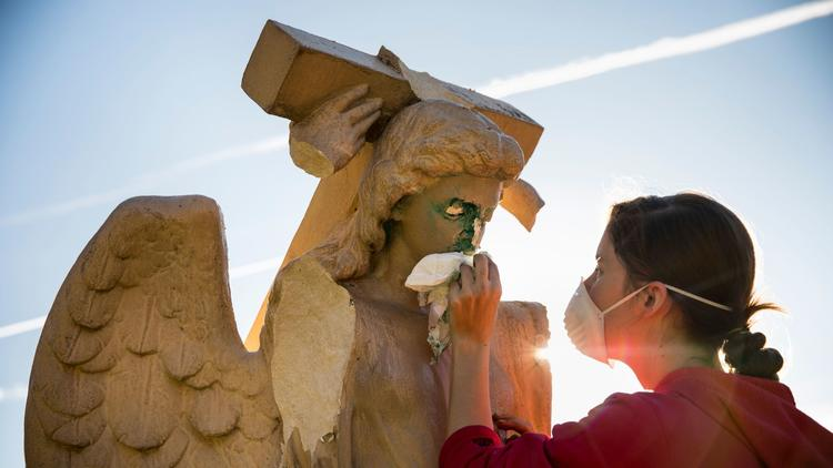 Evelyn Askew, 19, cleans an angel statue that was damaged and spray-painted with graffiti in front of Church of the Angels in Pasadena. (Credit: Jay L. Clendenin / Los Angeles Times)