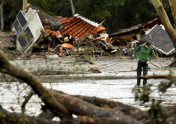 A man walks by destruction along Olive Mill Road in Montecito on Jan. 9, 2018. (Credit: Wally Skalij / Los Angeles Times)