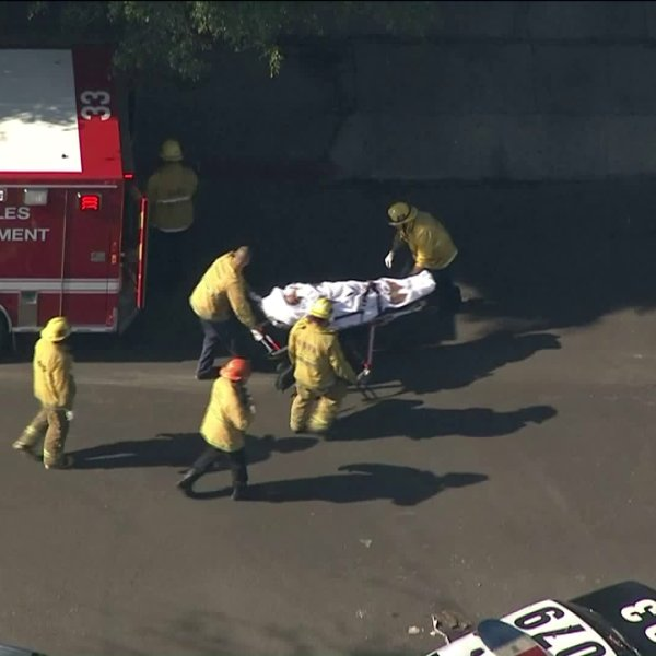 A body is carried on a stretcher following a police shooting in the Vermont Square neighborhood of South Los Angeles on Jan. 11, 2018. (Credit: KTLA)