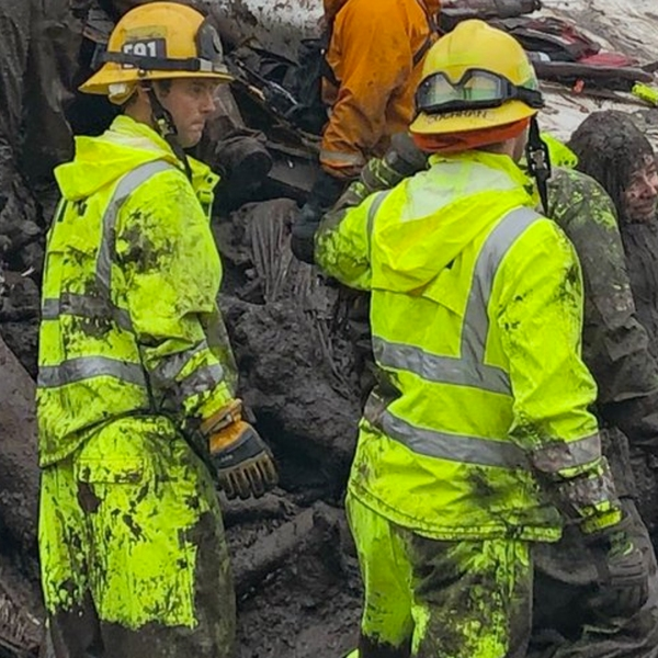 Rescuers sit with a girl who was pulled from the rubble of a home in Montecito on Jan. 9, 2018. (Credit: Santa Barbara County Fire Department)