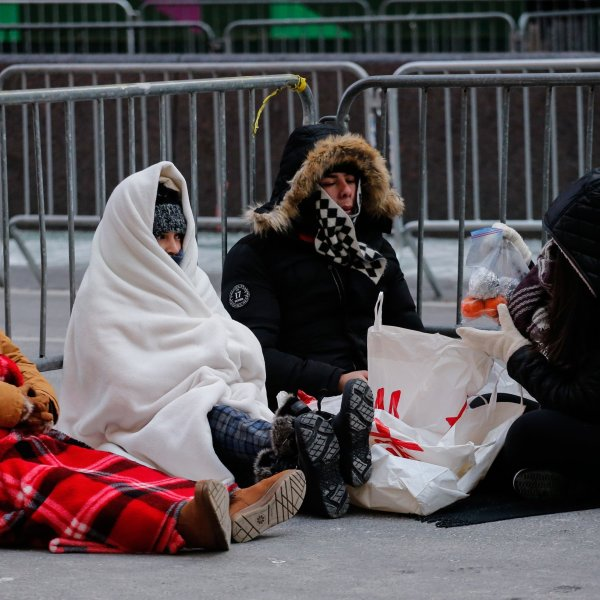 Revellers stay warm in Times Square early Sunday morning as they prepare for New Year's Eve celebrations. (Credit: Kena Betancur/AFP/Getty Images)