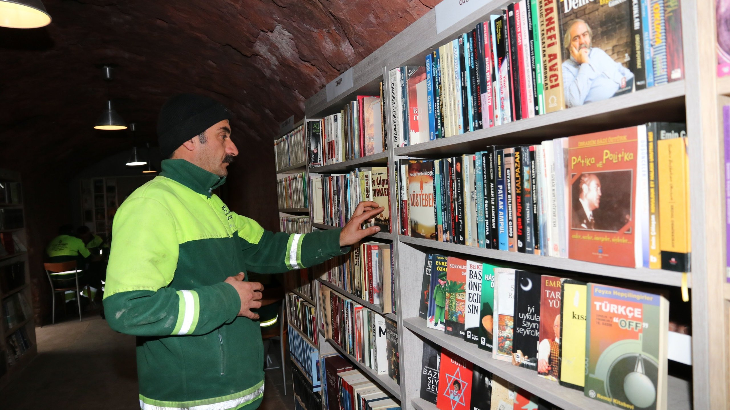 A garbage collector in Ankara browses for books at a library assembled from discarded books. (Credit: Çankaya Municipality Center via CNN)