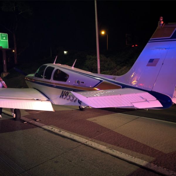 The pilot of a beachcraft bonanza that landed on the 55 Freeway in Costa Mesa talks on a cellphone on Jan. 28, 2018. (Credit: Costa Mesa Fire Department)