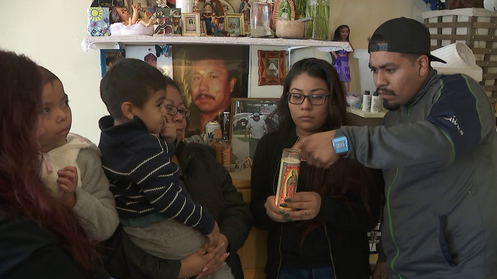 Lucio Garcia's family light a candle for a shrine set up in his honor on Jan. 11, 2018. (Credit: KTLA)