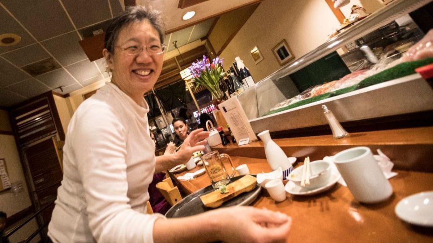 The mother of record-breaking Olympic skater Mirai Nagasu, Ikuko Nagasu, picks up dishes at a table at the family's Japanese restaurant Sushi Kiyosuzo in Arcadia in this undated photo. (Brian van der Brug / Los Angeles Times)