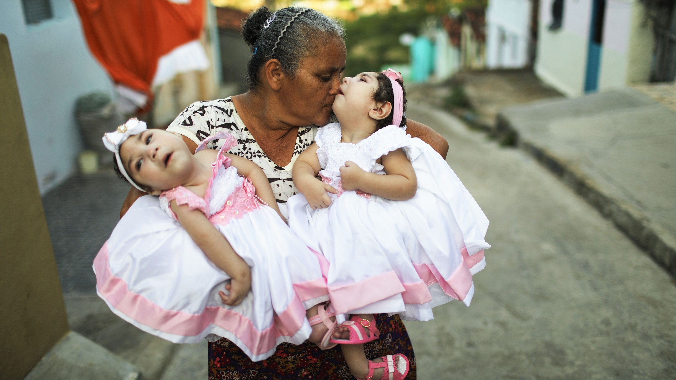 Grandmother Maria Jose holds her twin granddaughters Heloisa and Heloa Barbosa — both born with microcephaly after their mother contracted the Zika virus during pregnancy — outside of their house as they pose for photos at the twins' 1-year birthday party on April 16, 2017, in Areia, Brazil. (Credit: Mario Tama / Getty Images)