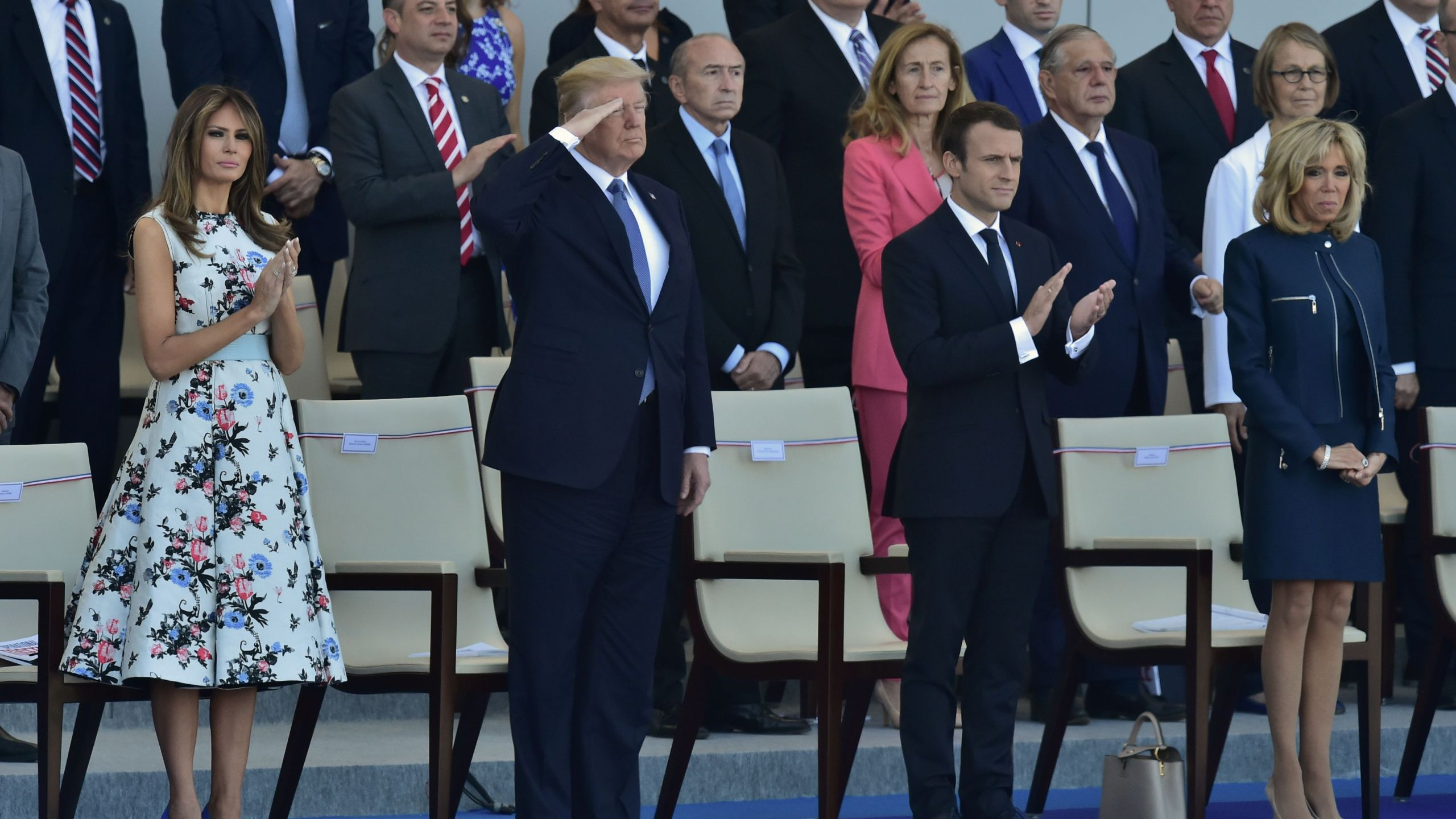 President Donald Trump salutes as French President Emmanuel Macron, his wife Brigitte Macron, and U.S. First Lady Melania Trump watch the annual Bastille Day military parade on the Champs-Elysees in Paris on July 14, 2017. (Credit: CHRISTOPHE ARCHAMBAULT/AFP/Getty Images)