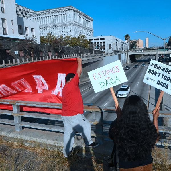 Volunteers from The Coalition for Humane Immigrant Rights (CHIRLA) protest with banners and placards over a freeway in Los Angeles on Aug. 28, 2017. (Credit: FREDERIC J. BROWN/AFP/Getty Images)