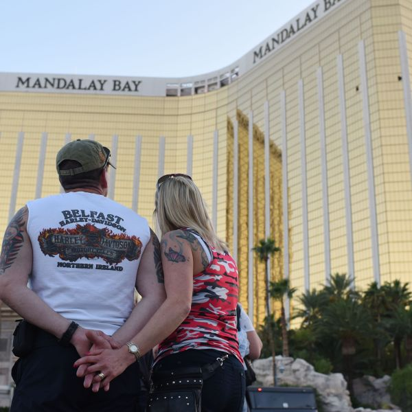 A couple stops on the Las Vegas Strip October 4, 2017, to look up at the two broken windows in the Mandalay Bay hotel from which killer Stephen Paddock let loose the worst mass shooting in modern American history. (Credit: ROBYN BECK/AFP/Getty Images)