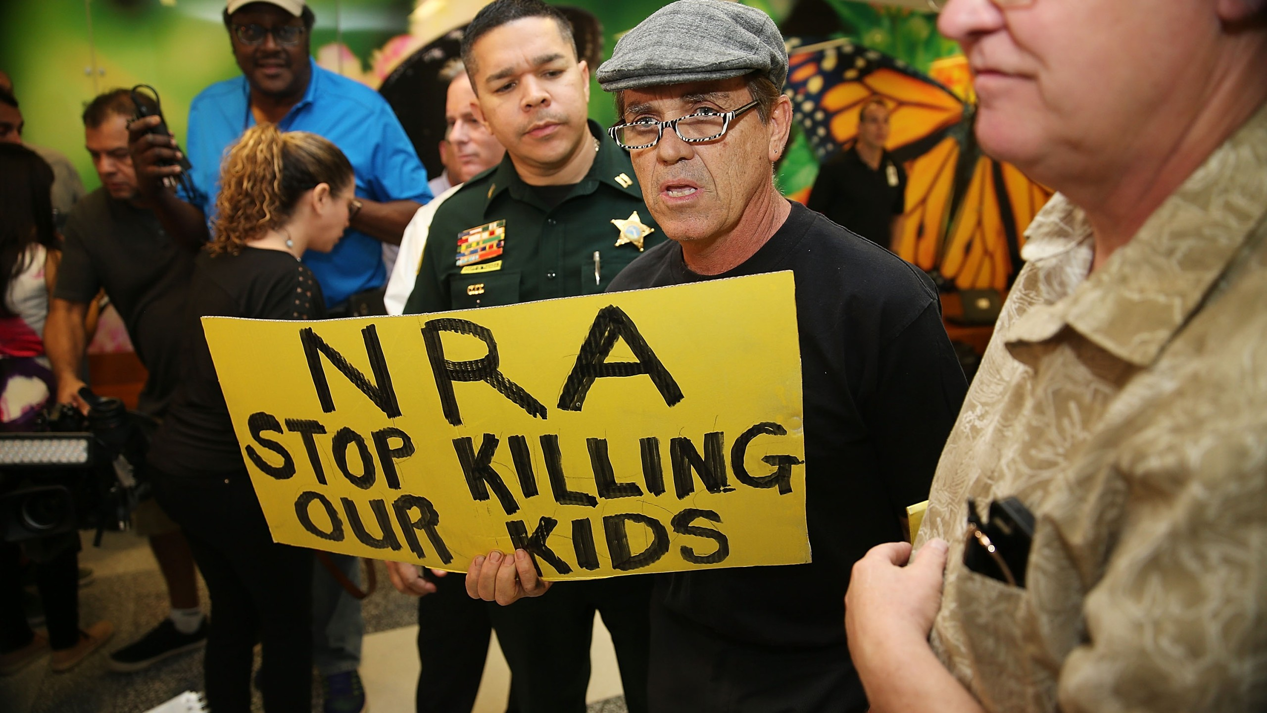 "A protester holds a sign that reads ""NRA Stop Killing Our Kids"" outside Broward County Courthouse, where Nikolas Cruz was having a bond hearing on Feb. 15, 2018 in Fort Lauderdale, Florida. (Credit: Charles Trainor Jr. - Pool/Getty Images)"