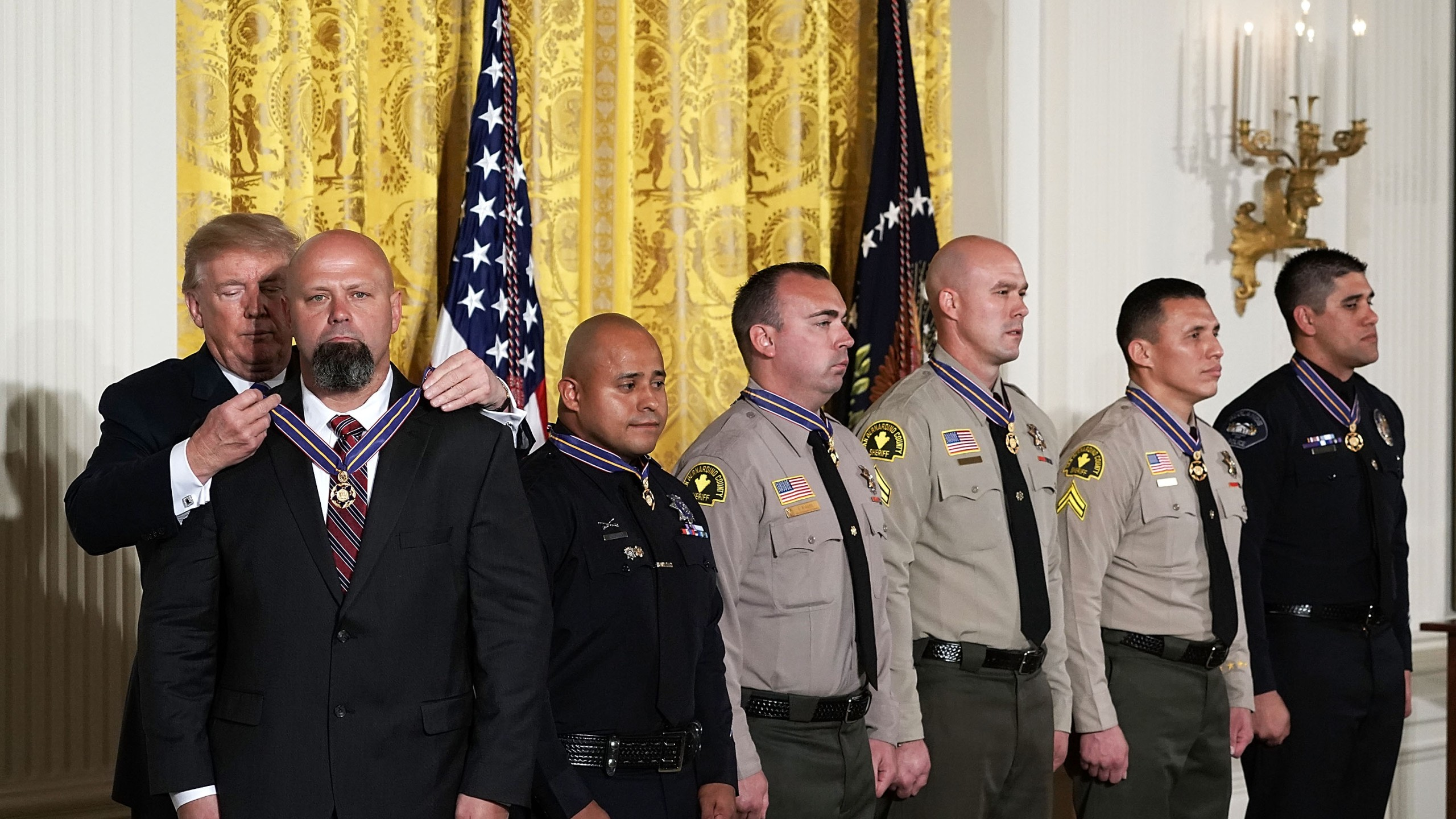 (Left to right) Donald Trump presents the Public Safety Medal of Valor to San Bernardino County District Attorney's Office Investigator Chad Johnson, San Bernardino Police Department Detective Brian Olvera, San Bernardino County Sheriff's Department Deputy Shaun Wallen, Detective Bruce Southworth, Corporal Rafael Ixco and Redlands Police Department Officer Nicholas Koahou during an award ceremony at the East Room of the White House on Feb. 20, 2018 in Washington, DC. (Credit: Alex Wong/Getty Images)