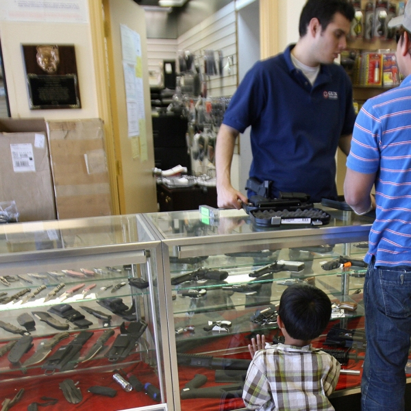 A man buys a gun, as his son waits for him at the Gun Gallery in Glendale on April 18, 2007. (Credit: Gabriel Bouys/AFP/Getty Images)