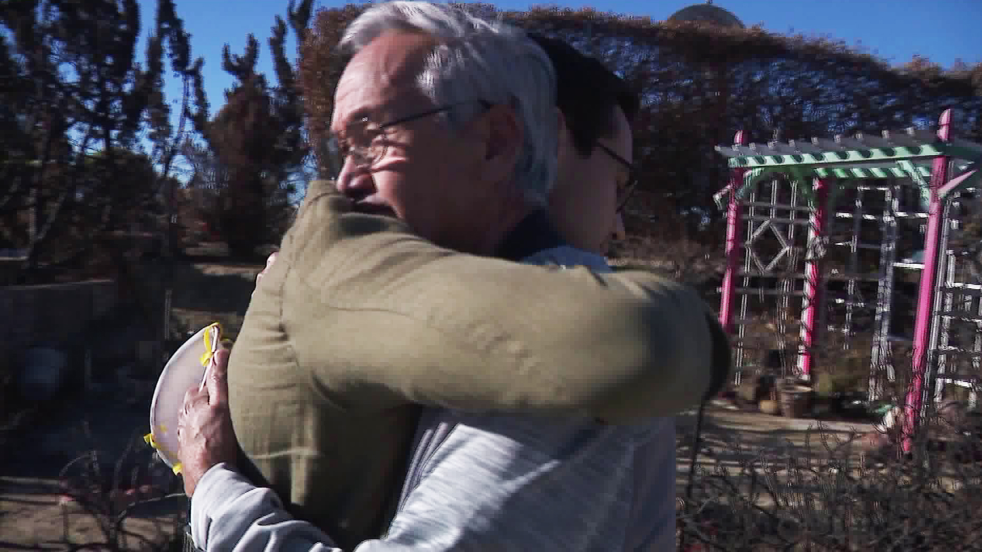 "Ansen ""Tony"" Roberts and Zach Garcia embrace at the site of Roberts' burned-out home that was destroyed in the Thomas Fire. (Credit: KTLA)"
