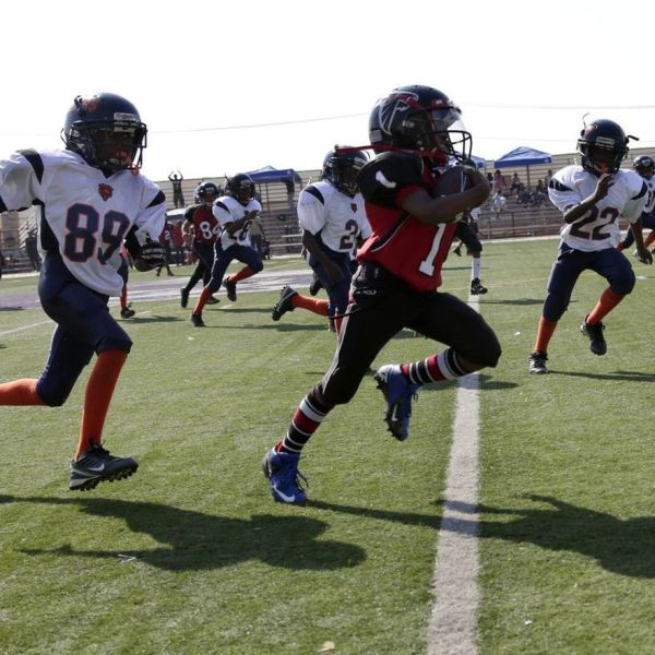 The LAPD-coached youth football team Watts Bears (in white) pursue a member of the Southern California Falcons during a 2013 game. (Credit: Irfan Khan / Los Angeles Times)