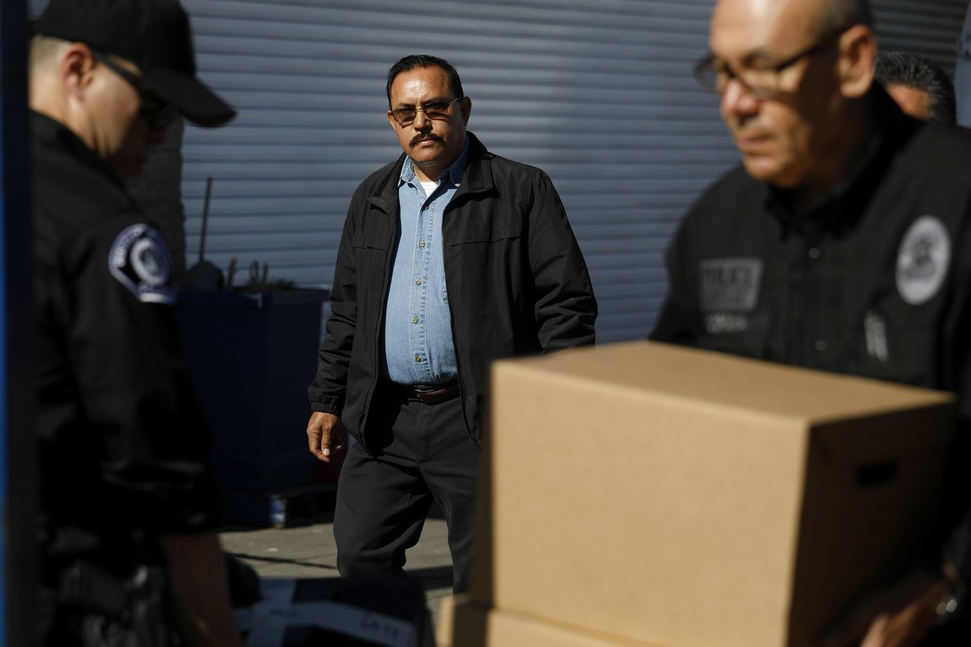 City of Maywood Mayor Ramon Medina walks with investigators from the Los Angeles County District Attorney's Office as they remove computers and boxes with files from his mechanic shop, R&M Auto Service Inc., on Feb. 8., 2018. (Credit: Gary Coronado / Los Angeles Times)
