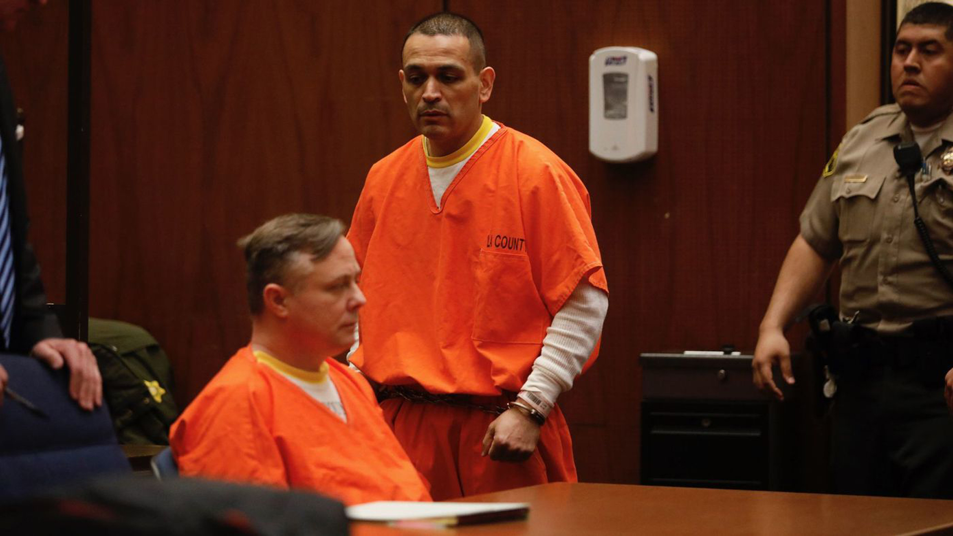 Los Angeles police officers James C. Nichols (seated) and Luis Valenzuela entered their no-contest pleas to sexually assaulting multiple women in a downtown Los Angeles courtroom. (Credit: Gary Coronado / Los Angeles Times)