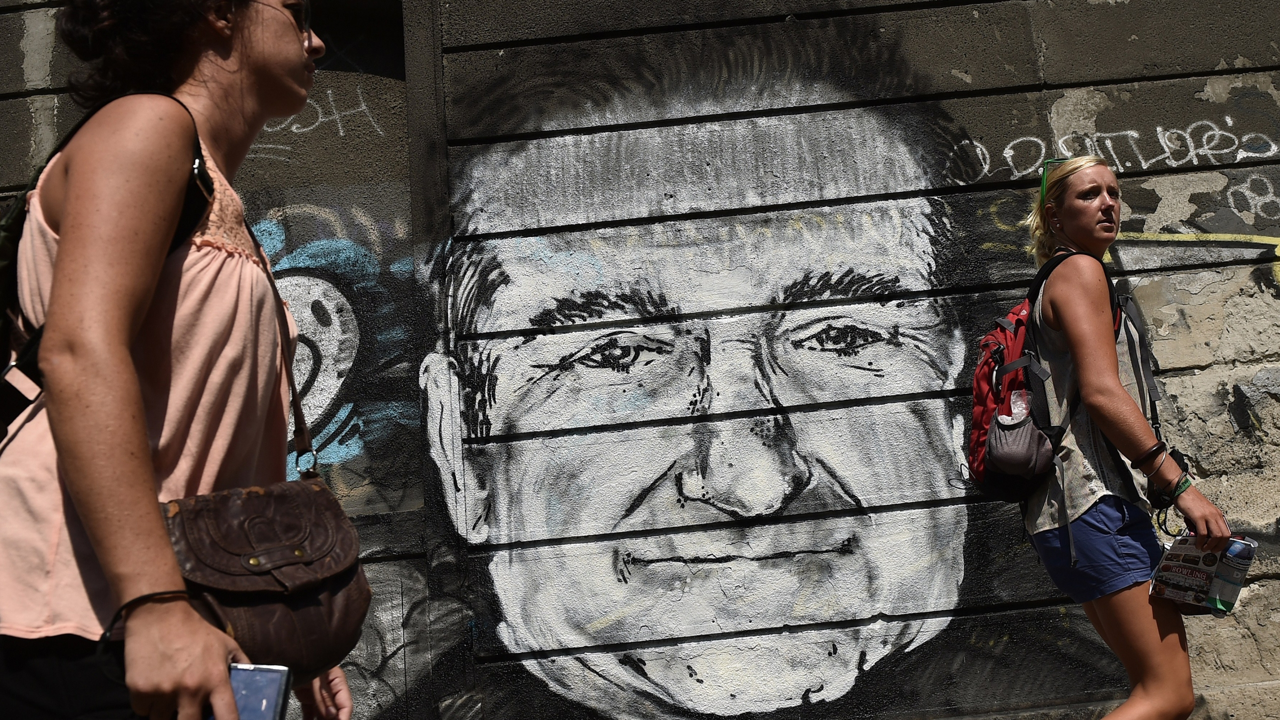 People walk past a mural depicting actor Robin Williams in downtown Belgrade on Aug. 13, 2014. (Credit: ANDREJ ISAKOVIC/AFP/Getty Images)