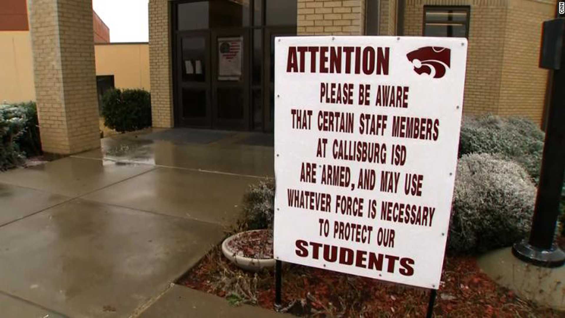 A sign warning visitors that some school staff are armed stands in front of a school entrance. (Credit: CNN)